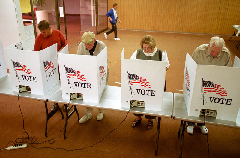 People using voting booths.