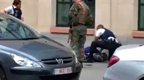 This screengrab shows police officials and a soldier looking at a man on the pavement in the city centre of Brussels on August 25, 2017, where a man is alleged to have attacked soldiers with a knife and was shot. © AFP