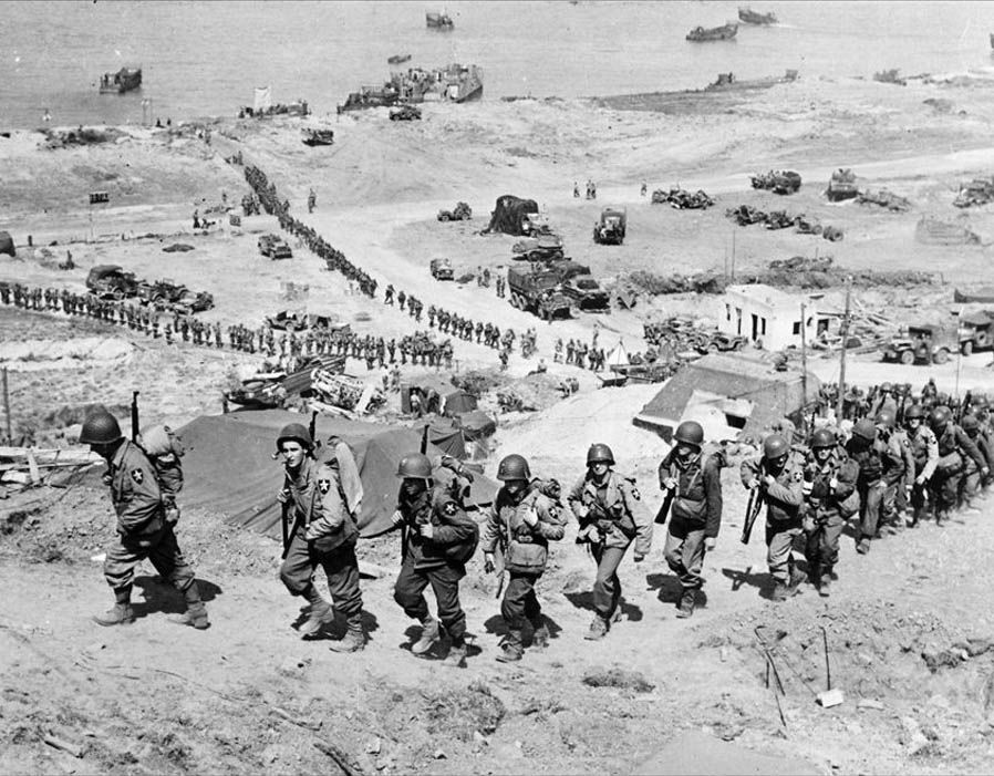 U.S. Army reinforcements march up a hill past a German bunker overlooking Omaha Beach after the D-Day landings near Colleville sur Mer, France, June 18, 1944