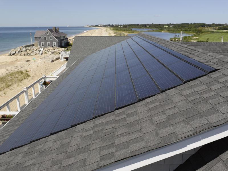 view of solar shingles and a beach
