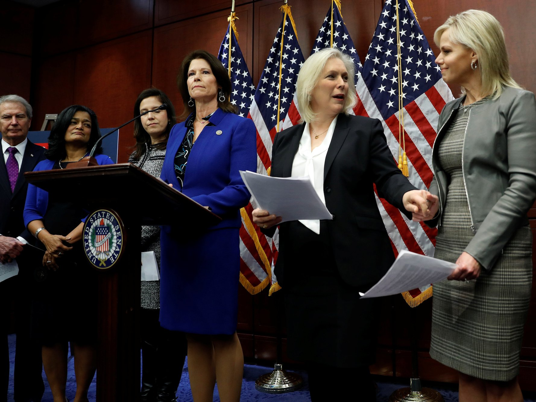Rep. Cheri Bustos speaks at a press conference calling for an end to forced arbitration as Sen. Kirsten Gillibrand greets Gretchen Carlson on Capitol Hill in Washington, U.S., December 6, 2017.