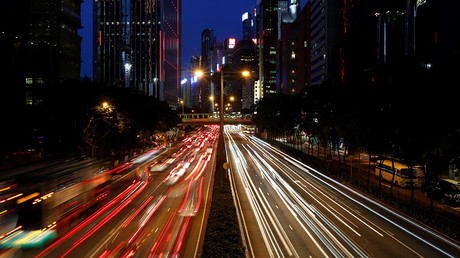 Traffic is seen between office buildings at sunset in downtown Hong Kong, China  © Bobby Yip