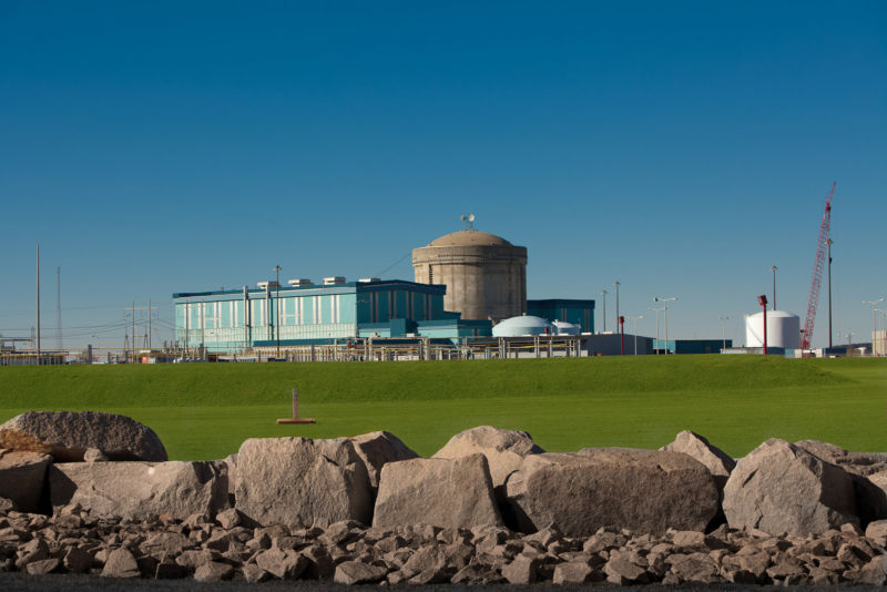 A nuclear plant in a grassy field during the summer.