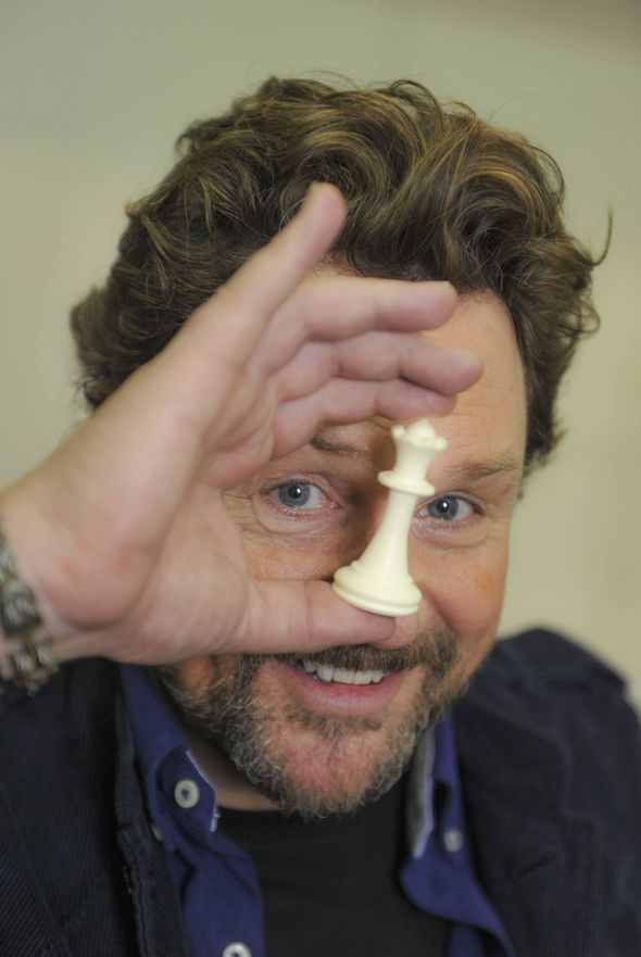Michael Ball holding a chess piece