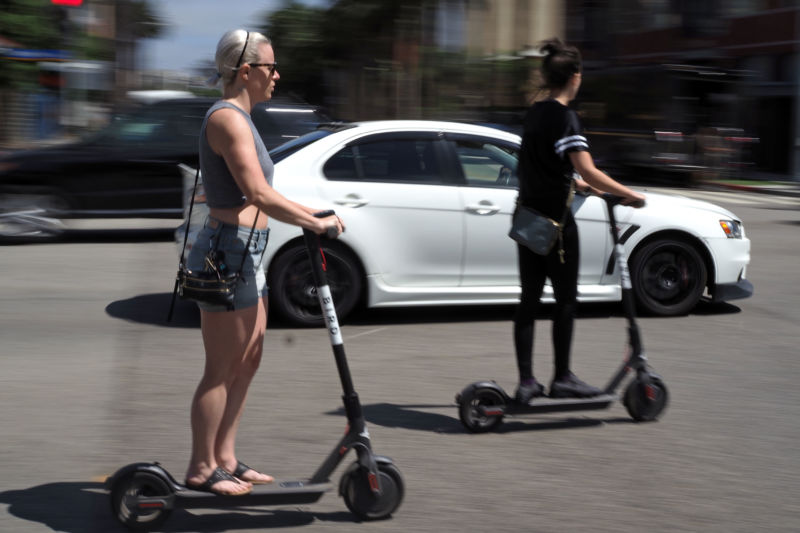 People ride shared electric scooters in Santa Monica, California, on July 13, 2018.