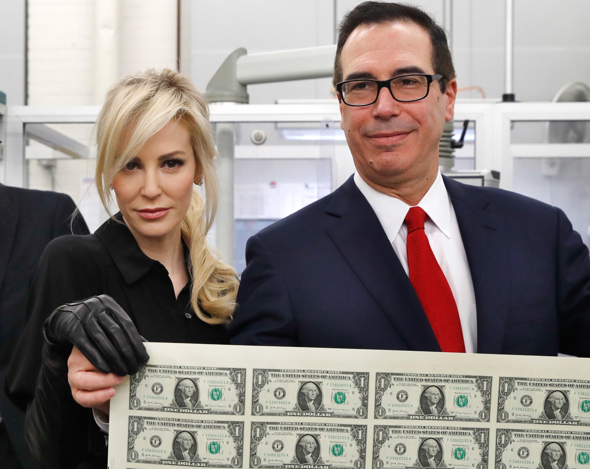 Treasury Secretary Steven Mnuchin, right, and his wife Louise Linton, hold up a sheet of new $  1 bills, the first currency notes bearing his and U.S. Treasurer Jovita Carranza's signatures, Wednesday, Nov. 15, 2017,