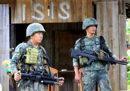 FILE PHOTO: Soldiers stand guard along the main street of Mapandi village as government troops continue their assault on insurgents from the Maute group, who have taken over large parts of Marawi City, Philippines June 2, 2017. REUTERS/Romeo Ranoco