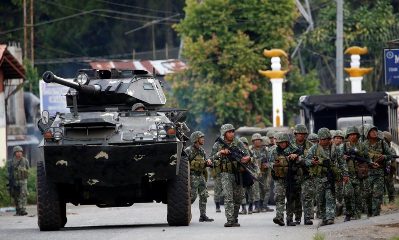 Members of Philippine Marines walk next to an armoured fighting vehicle (AFV) as they advance their position in Marawi City, Philippines May 28, 2017. REUTERS/Erik De Castro