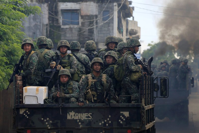Soldiers onboard military trucks ride along the main street as government troops continue their assault on insurgents from the Maute group, who have taken over large parts of Marawi City, Philippines. REUTERS/Romeo Ranoco