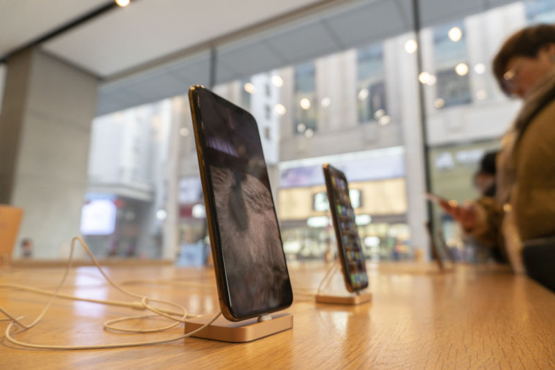 Close-up image of phones prominently displayed on a wooden table in a brightly lit, streetside store.