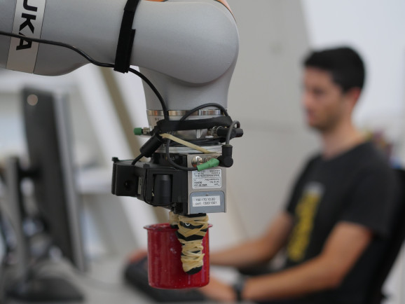 Manuelli uses the DON system and Kuka robot to grasp a cup