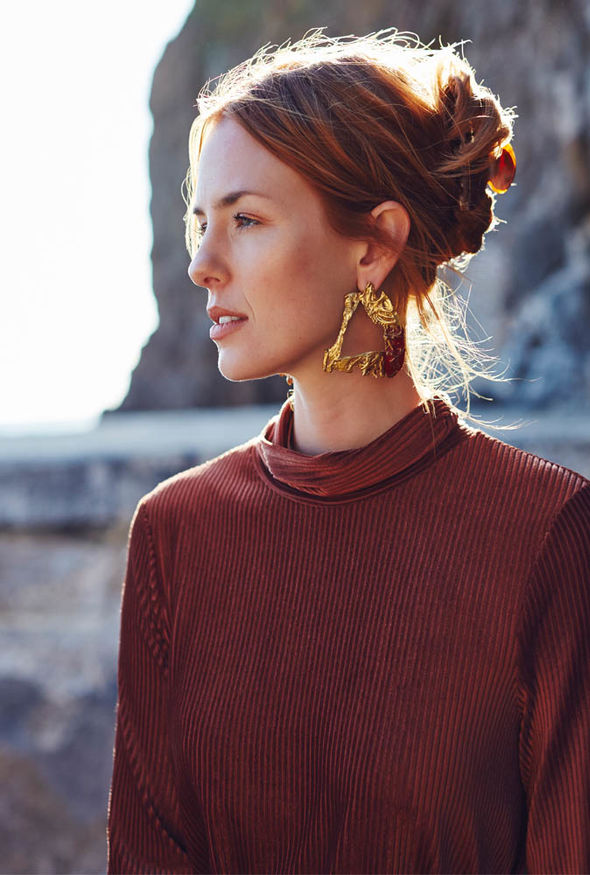 Model wears large gold earring