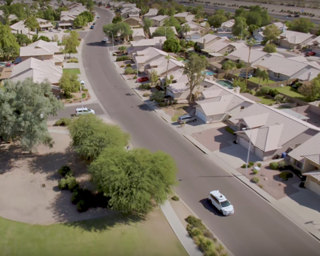 """This is a screenshot from Waymo's <a href=""""https://www.youtube.com/watch?v=aaOB-ErYq6Y"""">November 2017 video</a> announcing the start of fully driverless testing. It shows fully driverless Waymo cars driving on residential streets that are almost empty."""