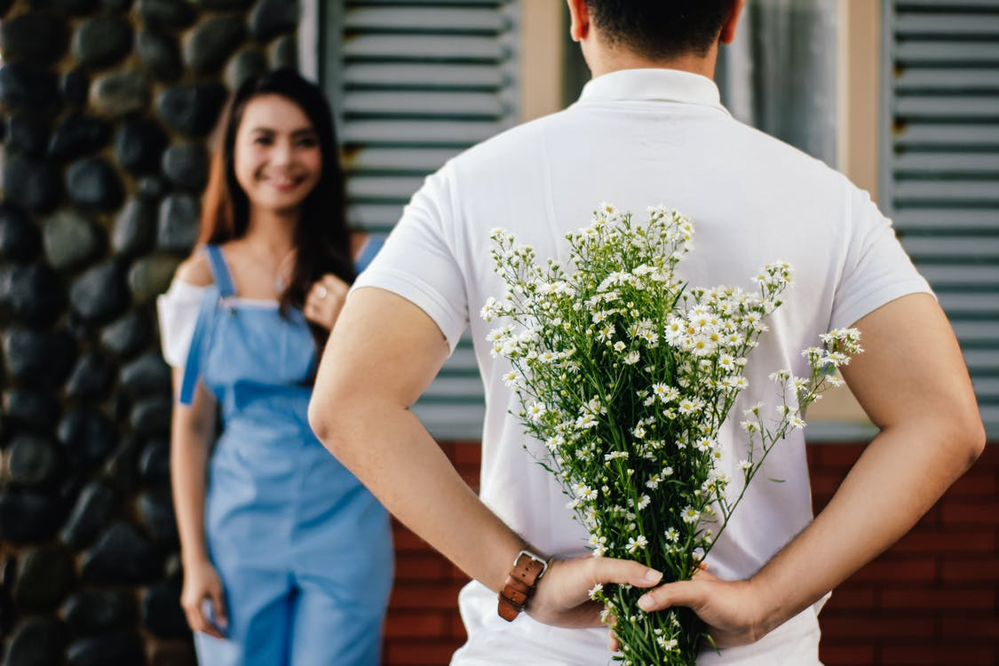 Man Holding Flowers in front of Woman